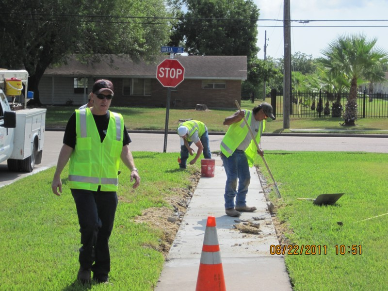 Workers performing maintenance on a sidewalk