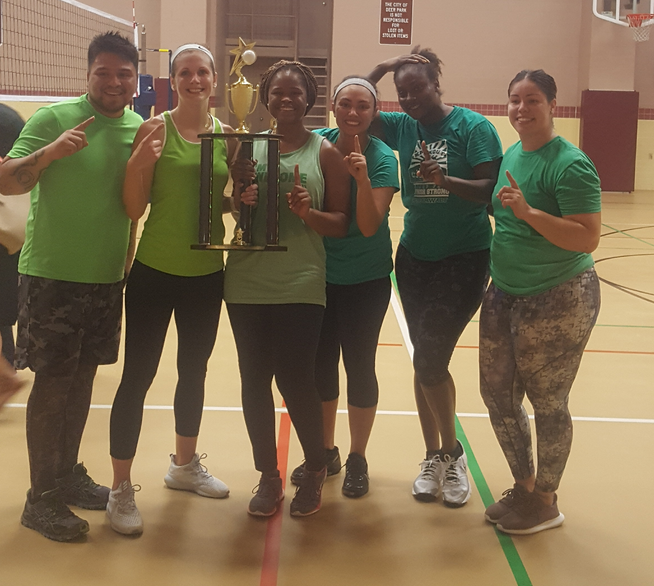 Volleyball winners smiling and holding a trophy