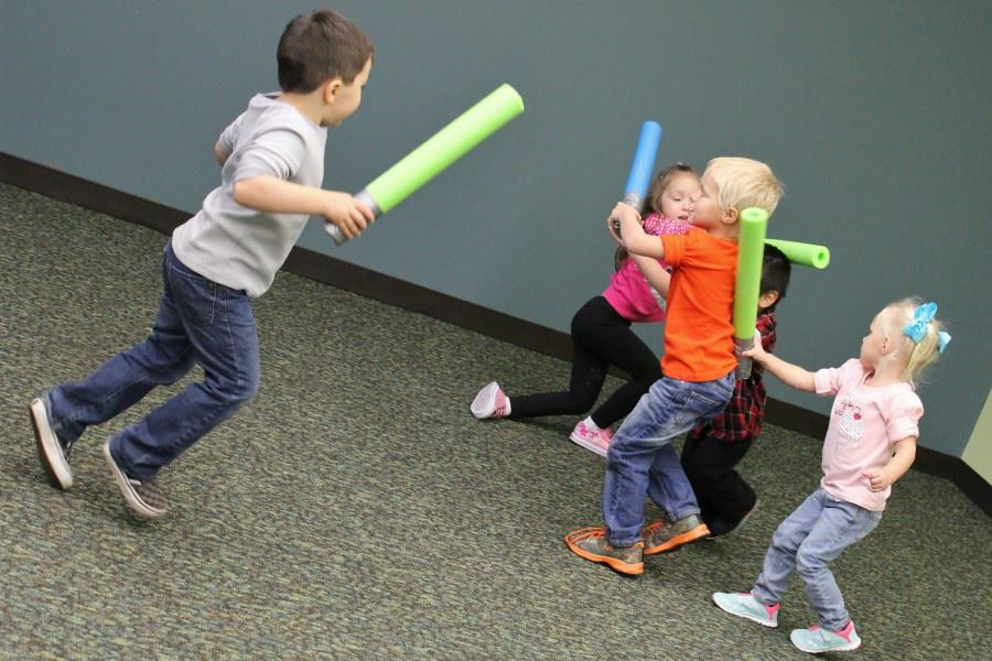 young kids playing with pool noodles